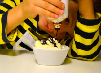 Bruno häller chokladsås över vaniljglassen